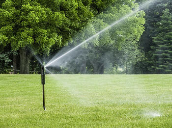 Tall sprinkler spraying lawn with long jet of water on college campus